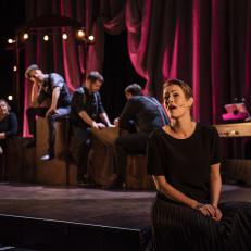 Naisnäyttelijä laulaa taustallaan ryhmä ihmisiä istumassa