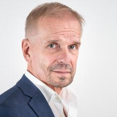 Jukka Puotila valkoisella taustalla, päällään sininen puku.