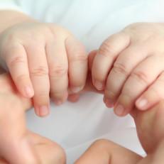 vauva pitää aikuisen etusormista kiinni