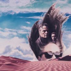 Hiekkadyyni, jonka takaa näkyvät naisen kasvot aurinkolaseissa.