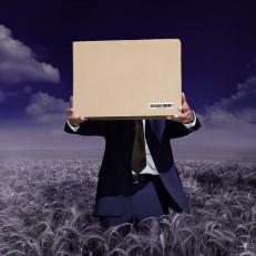 Pukumies viljapellolla ojentaa ruskeaa pahvilaatikkoa katsojaa kohti.