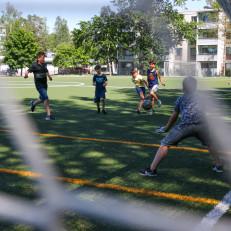 Kivakesä kulmilla -toimintaan osallistuvat lapset pelaavat jalkapalloa. Kuva kuvattu maalin verkon läpi.