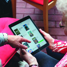 Omakirjasto-kummi opastaa iäkästä rouvaa tabletin käytössä.