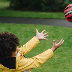 Lapsi heittää palloa.