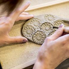 Kädet kaivertavat koristekuviota savikiekkoon.