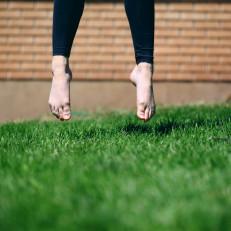 Henkilö hyppää ruohikolla.
