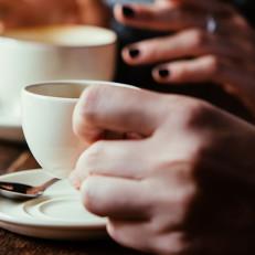 Kaksi kahvikuppia pöydällä, joista kahvin juojat pitävät kupin korvista kiinni.