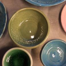 Eri väreillä lasitettuja keramiikkakulhija ja lautasia.